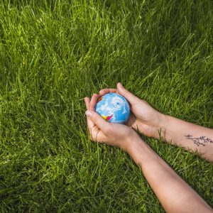 an-overhead-view-of-hands-holding-globe-ball-on-green-grass-min-scaled-min